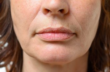 59848626 - closeup on the mouth of a middle-aged brunette woman with her mouth closed and a serious expression